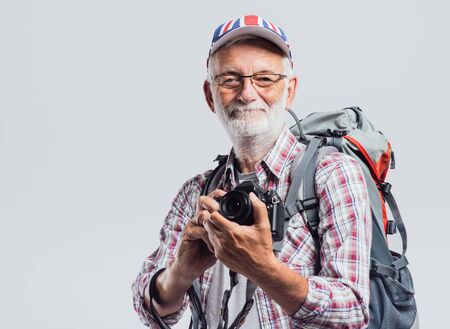 white beard: Senior tourist photographer with backpack and digital camera, he is wearing a British flag cap