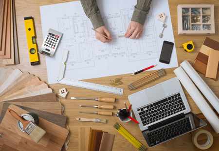 quantity surveyor: Construction engineer and architects desk with house projects, laptop, tools and wood swatches top view, male hands drawing
