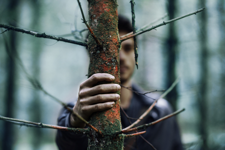 foreground focus: Young man hiding in the woods and holding a trunk, hand on foreground, selective focus Stock Photo
