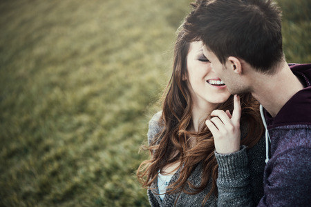 Young loving couple sitting on grass, she is flirting with him, love and relationships concept