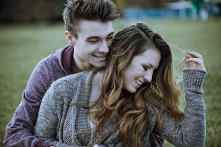 pareja abrazada: Juguetona pareja de jóvenes sentados en la hierba y abrazos, que se están riendo y disfrutando