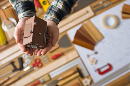 손 모델 하우스, 배경 테이블, 집 보험 개념에 도구 및 청사진 프로젝트 작업 테이블을 들고