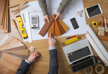 デスクトップの上面に彼の顧客、ラップトップ、ツール、家プロジェクトに木材の見本を示すインテリア デザイナー 写真素材