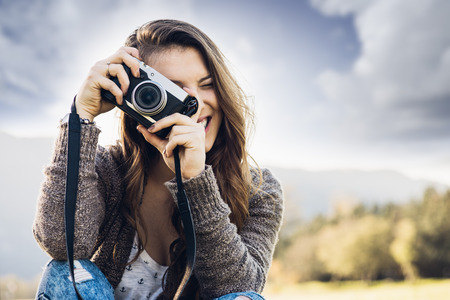 camera girl: Young female photographer sitting on the grass and taking pictures, natural landscape on background