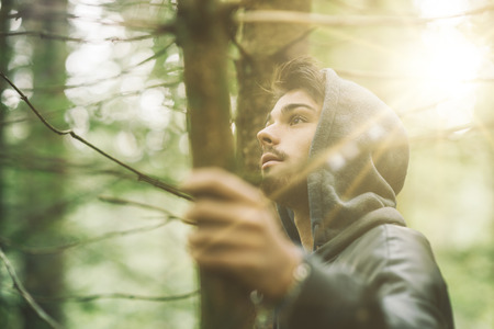 Hooded guy in the woods exploring nature, individuality and freedom concept