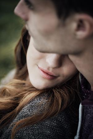 Jonge verliefde paar ontspannen op het gras en knuffelen, is ze glimlachend en leunend op zijn schouder, relaties en gevoelens begrip Stockfoto