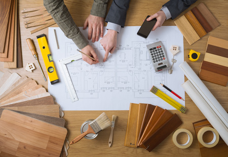 Üzleti ember dolgozik együtt egy építési projekt, asztali felülnézetben szerszámok, faipari színminták, mobiltelefon és tervrajz