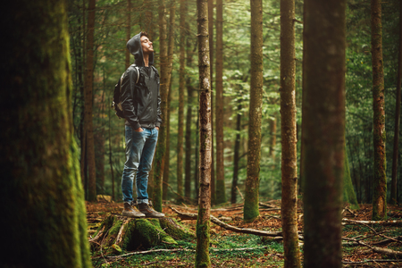 Hooded young man standing in the forest and exploring, freedom and nature concept