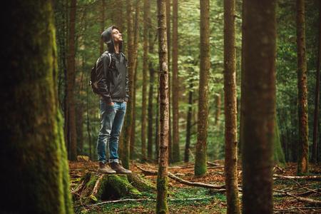 Hooded jonge man in het bos en het verkennen, de vrijheid en de natuur-concept