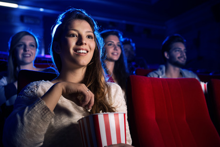 at the theater: Young smiling woman watching a film in the movie theater and eating popcorn, entertainment and cinema concept
