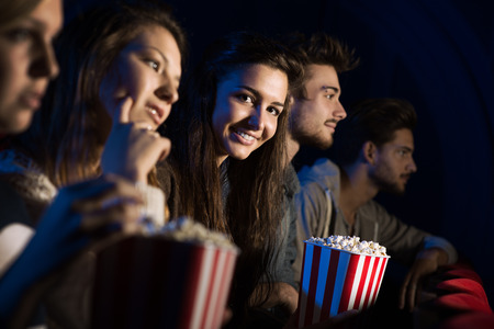 movie: Group of teenager friends at the cinema watching a movie together and eating popcorn, entertainment and enjoyment concept