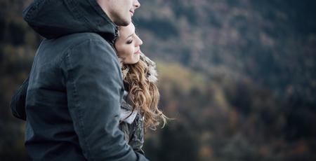 parejas romanticas: joven pareja romántica de citas en invierno, que están sentados juntos, ella se apoya en el hombro de su novio