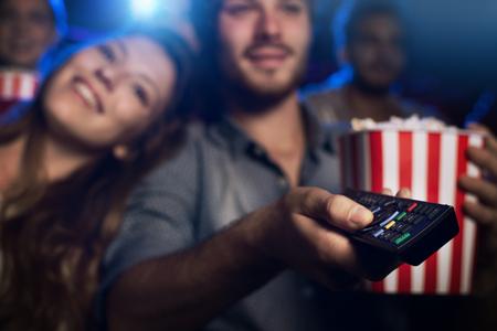 Junger Mann, einen Film mit seiner Freundin zu beobachten und zeigt eine Fernbedienung: Kino, Unterhaltung und Heimkino-Konzept