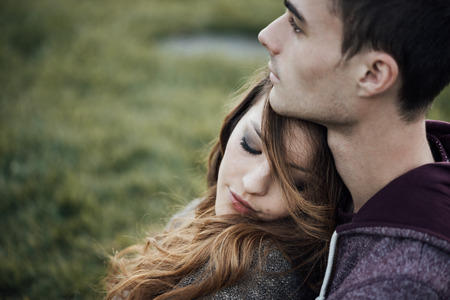Young loving couple relaxing on grass and hugging, she is smiling and leaning on his shoulder, relationships and feelings concept Archivio Fotografico