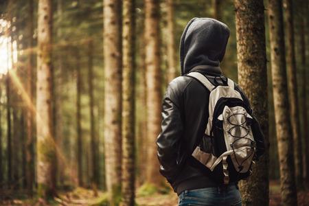 Mladý muž v kápi turistika v lese, svobody a příroda koncepce