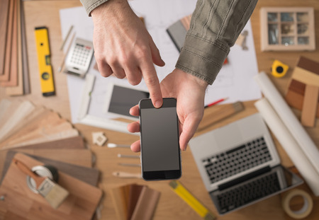 Home decorator's hands holding a mobile touch screen phone, desktop with tools, laptop and wood swatches on background, top view