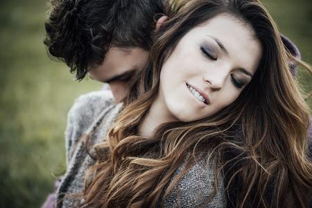 parejas enamoradas: Pareja romántica al aire libre, que están sentados en el césped y abrazos, ella se mordía el labio