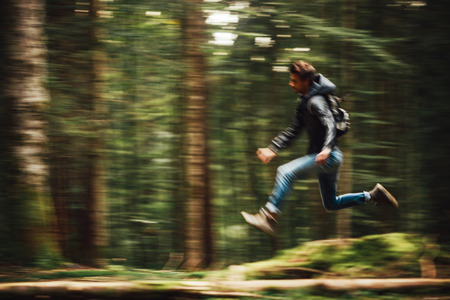 woods: Hooded young man with backpack running in the forest Stock Photo