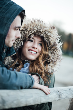 teen love: Smiling loving couple with hoods dating during a cold winter day, love and relationships concept