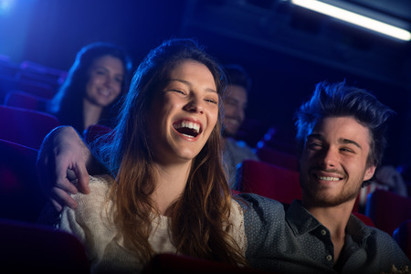 Young loving couple at the cinema watching a movie and smiling, people sitting on background