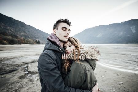 romance: Jovem amorosa casal abraçado, lago e montanhas no fundo, amor e Conceito do romance