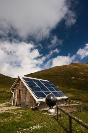 electrical energy: Solar panels on a mountain hut, electrical energy production and environmental conservation concept Stock Photo