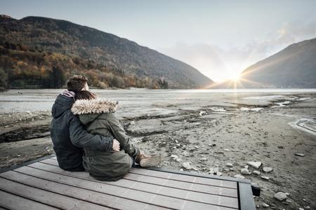 parejas amor: Amantes de la pareja sentada en un muelle, abrazando y mirando a otro lado, el amor y los sentimientos concepto