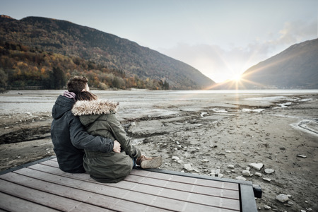 couples in love: Loving couple sitting on a pier, hugging and looking away, love and feelings concept Stock Photo