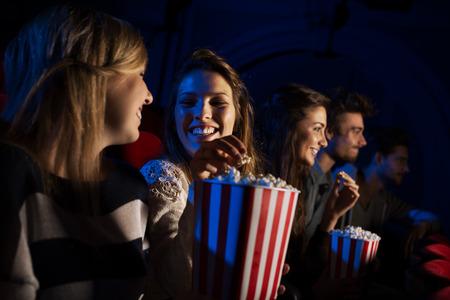 juventud: Grupo de amigos adolescentes en el cine viendo una película juntos y comiendo palomitas de maíz, el entretenimiento y el disfrute concepto