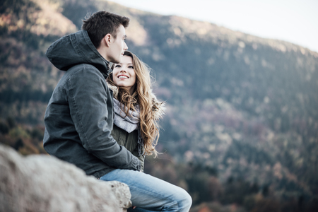 young couple smiling: Romantic young couple dating in winter, they are sitting together, she is looking at her boyfriend Stock Photo