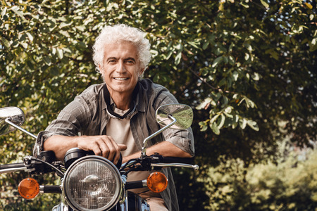 hombre viejo: hombre guapo confía en que monta una moto de época y sonriendo a la cámara