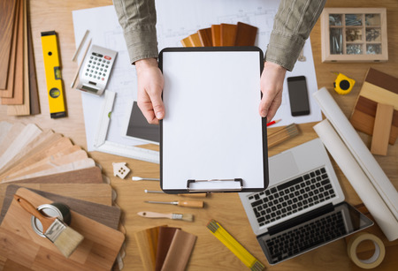 Home improvement and renovation concept with hands holding a blank clipboard and work desktop on background, top view