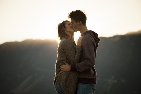 Romantic young couple kissing passionately at sunset, mountains on background, feelings and relationships concept