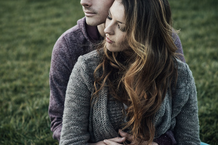 Romantic couple outdoors, they are sitting on grass and hugging, love and relationships concept Foto de archivo