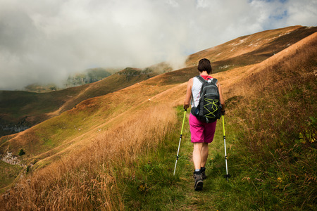 healthy path: Woman hiking using hiking poles, nordic walking and outdoor sports concept Stock Photo