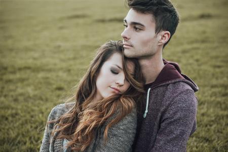 pareja de adolescentes: adolescentes j�venes al aire libre, sentados en el c�sped y caricias, que est� abrazando a su novia, relaciones y sentimientos concepto