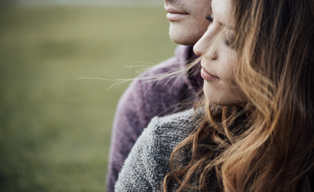 Young loving couple outdoors sitting on grass, hugging and looking away, future and relationships concept