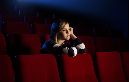Young lonely woman at the cinema leaning on the seat in front of her and watching a movie