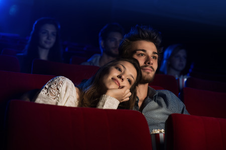 movies: Young loving couple at the cinema watching a movie, he is hugging her girlfriend