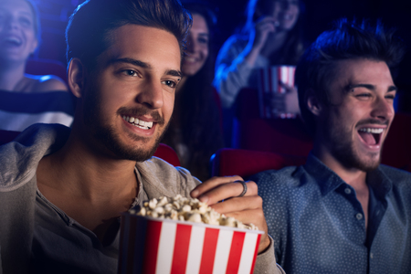 Young people sitting at the cinema, watching a movie and eating popcorn, two smiling men on foreground