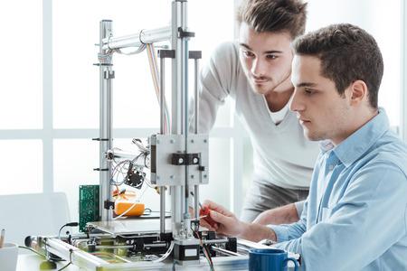 jovenes estudiantes: j�venes estudiantes en el laboratorio utilizando una impresora 3D, la tecnolog�a y el concepto de la educaci�n Foto de archivo