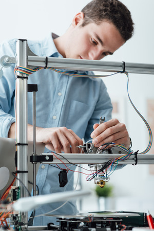 Young efficient engineer working on a 3D printer and adjusting components Imagens