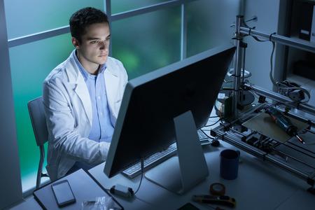 Zelfverzekerd techniek student die in het laboratorium en het gebruik van een computer, een 3D-printer op de achtergrond, technologie en innovatie-concept