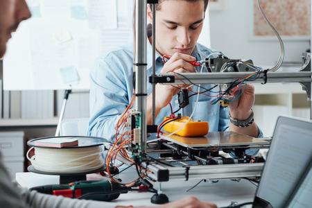Studenti, sedící u stolu laboratoři a pomocí 3D tiskárny pro výrobu prototypů