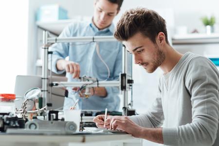 Estudiantes de ingeniería que trabajan en el laboratorio, un estudiante está usando una impresora 3D en el fondo Foto de archivo