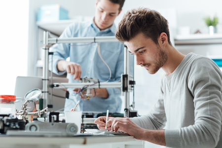 laboratorio: Estudiantes de ingenier�a que trabajan en el laboratorio, un estudiante est� usando una impresora 3D en el fondo Foto de archivo