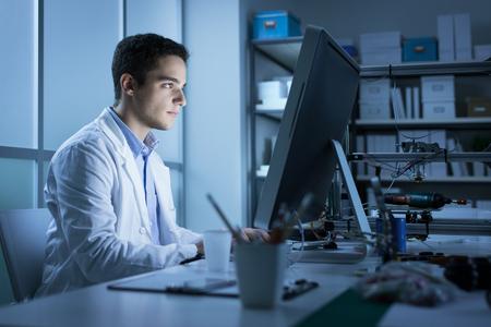 Zelfverzekerd techniek student die in het laboratorium en het gebruik van een computer, een 3D-printer op de achtergrond, technologie en innovatie-concept Stockfoto