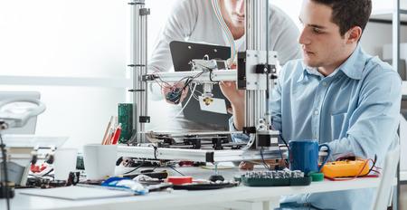 ingenieria elÉctrica: Ingeniería estudiantes usando una impresora 3D innovadora en el laboratorio Foto de archivo