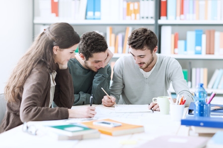 웃는 대학생의 그룹은 도서관에서 함께 공부하고 프로젝트 작업 스톡 콘텐츠