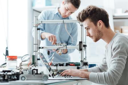 studenci inżynierii pracujących w laboratorium, student jest dostosowanie elementów drukarki 3D, drugi jeden na pierwszym planie jest za pomocą laptopa